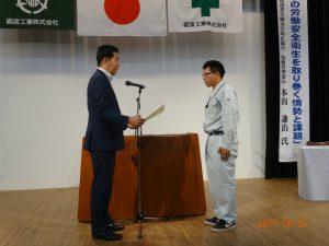 安全衛生優良表彰を受ける 土木部 菊池 学さん(山王川用水路工事における安全管理活動報告もしてもらいました)