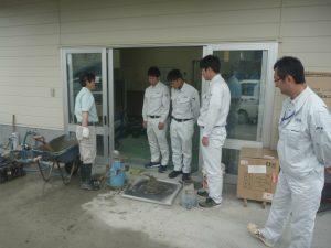 富山菱光コンクリート工業さんの試験室前でコンクリートの試験について説明を受ける3名の新入社員です。
