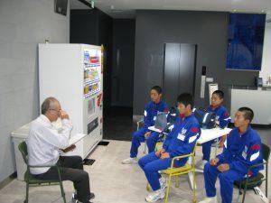 朝一番に集合後に建築部の米田さんから今日の予定と注意事項を聞いています。
