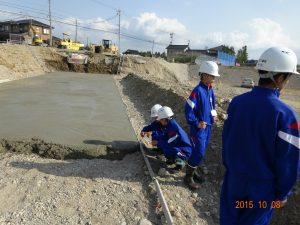 調整池の底では(右側)ショベルカーが動いています。興味深々。 左の二人はコンクリートが固まりかけている状態を手で触っています。