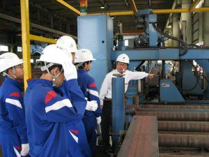 トナミ鉄工の工場の穿孔機の説明を受けています。